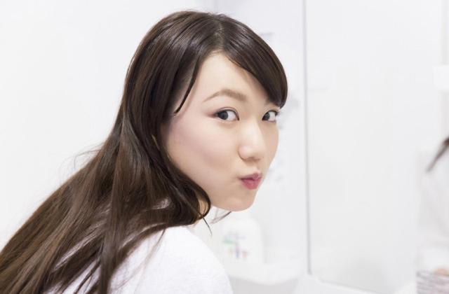 オイルプリングで歯を白くする女性